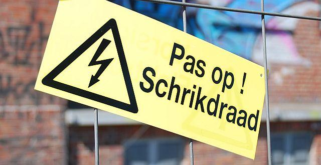 """Schild an der Uni Münster zur Sprachforschung: """"Pass auf! Elektrozaun"""""""